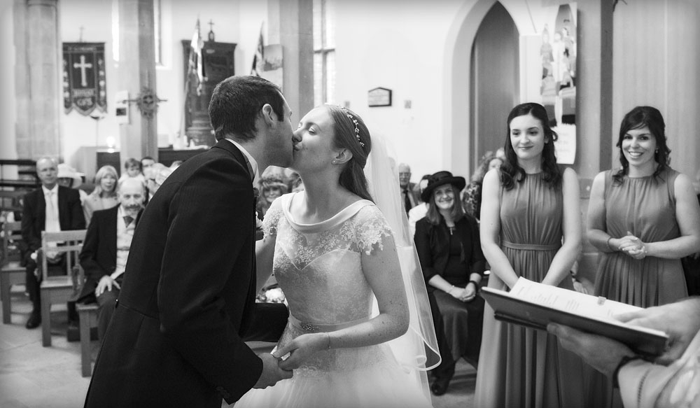 black and white bride and groom first kiss church, warwickshire wedding photographer, Ansty Hall