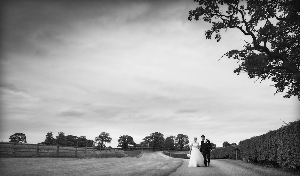 black and white, bride and groom walking hand in hand, cheshire wedding photographer, sandhole oak barn