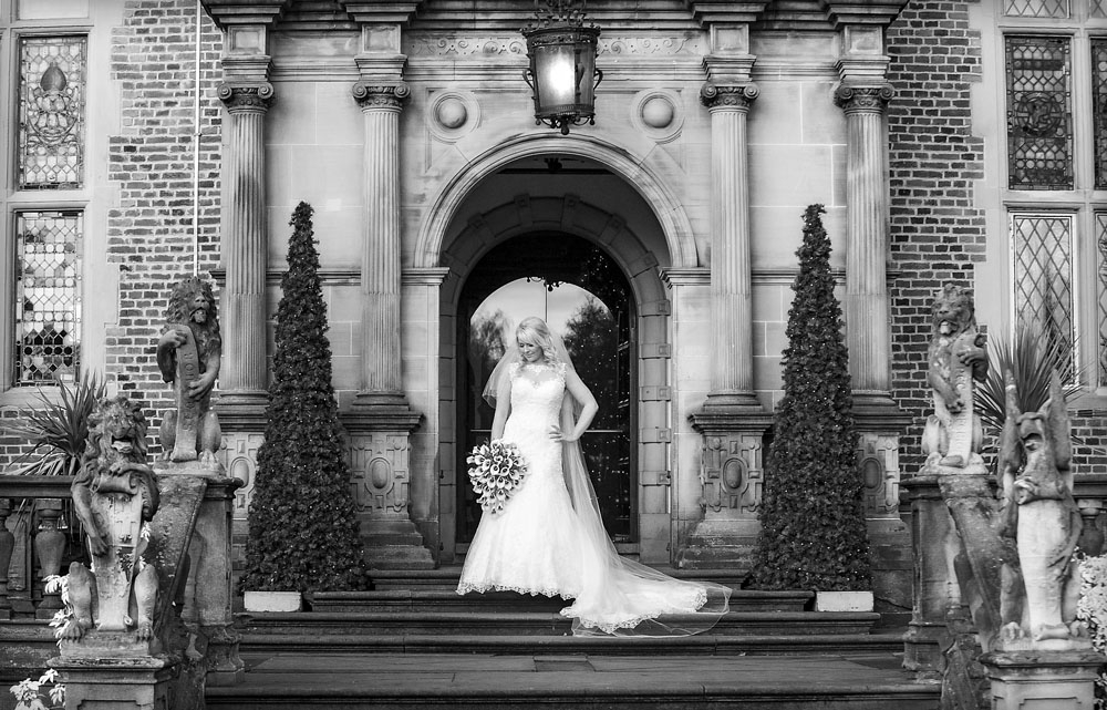 bride standing in archway, black and white, cheshire wedding photographer, crewe hall