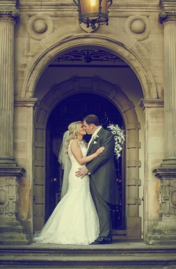 bride and groom kissing in archway, cheshire wedding photographer, crewe hall