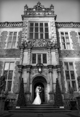 bride and groom kissing in archway, black and white, cheshire wedding photographer, crewe hall