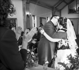 bride and groom first kiss, barn, wedding photographer in wales