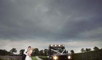 bride and groom kiss by land rover defender, cheshire wedding photographer, sandhole oak barn