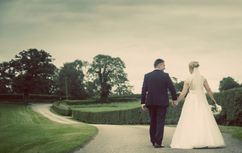 bride and groom walking hand in hand, cheshire wedding photographer, sandhole oak barn