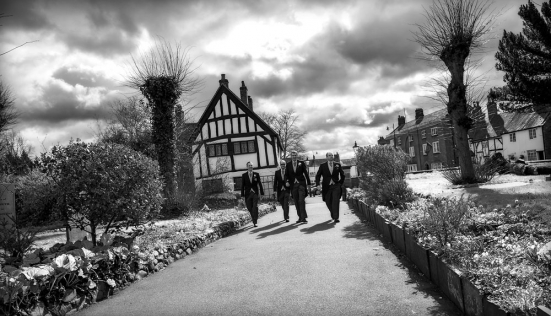 black and white groom and best man walking to church, warwickshire wedding photographer, Ansty Hall